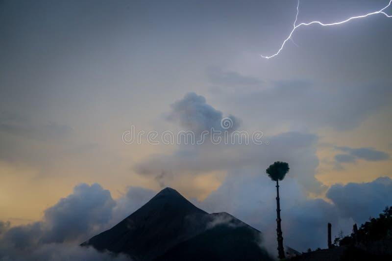 Nattåskastorm Blixt med solnedgång och moln över vulkan Fuego royaltyfri fotografi