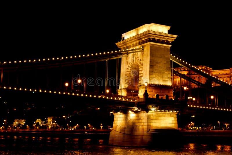 Natt Budapest som gl?der i guld Kedjebron ?ver Donauen exponeras av ljusa kulor foto fr?n floden royaltyfri bild