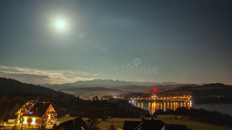 Natt med månen, stjärnor, moln, berg och byn nära sjön royaltyfri fotografi