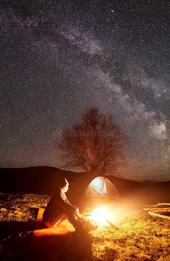 Natt som campar i berg Kvinnlig fotvandrare som vilar nära lägereld, turist- tält under stjärnklar himmel arkivbilder