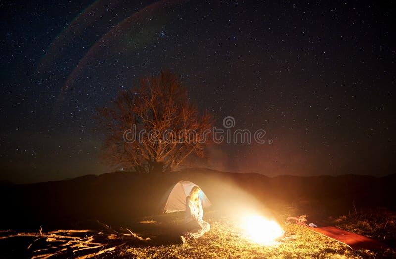 Natt som campar i berg Kvinnlig fotvandrare som vilar nära lägereld, turist- tält under stjärnklar himmel royaltyfri foto