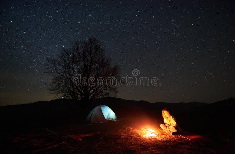 Natt som campar i berg Kvinnlig fotvandrare som vilar nära lägereld, turist- tält under stjärnklar himmel royaltyfria foton