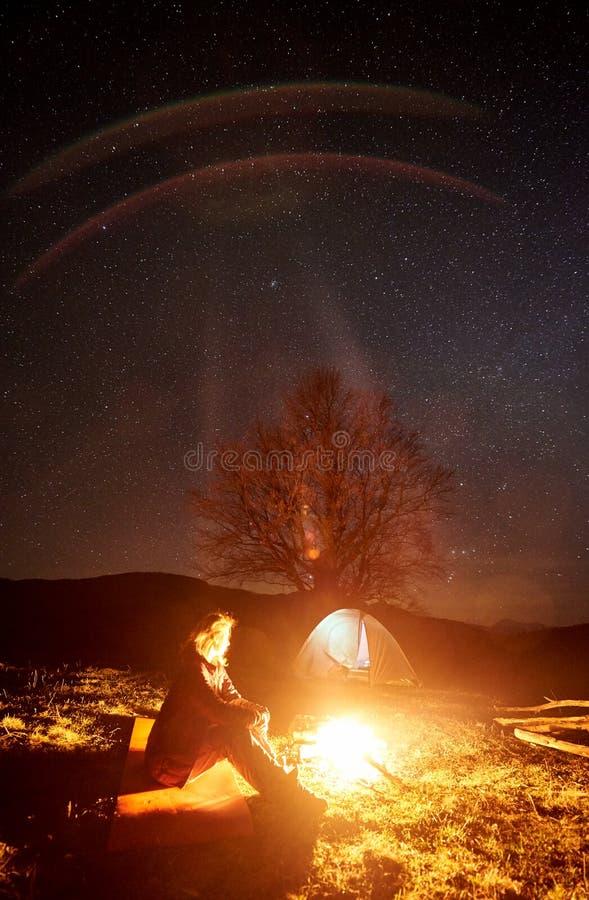 Natt som campar i berg Kvinnlig fotvandrare som vilar nära lägereld, turist- tält under stjärnklar himmel royaltyfri fotografi