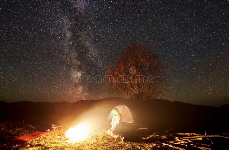 Natt som campar i berg Kvinnlig fotvandrare som vilar nära lägereld, turist- tält under stjärnklar himmel arkivbild