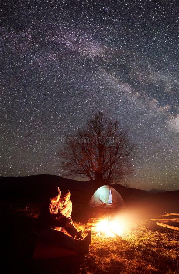 Natt som campar i berg Parfotvandrare som har, vilar nära lägereld, turist- tält under stjärnklar himmel royaltyfri bild