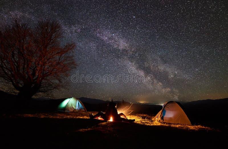 Natt som campar i berg Parfotvandrare som har, vilar nära lägereld, turist- tält under stjärnklar himmel arkivbild