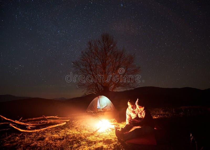 Natt som campar i berg Parfotvandrare som har, vilar nära lägereld, turist- tält under stjärnklar himmel royaltyfri fotografi