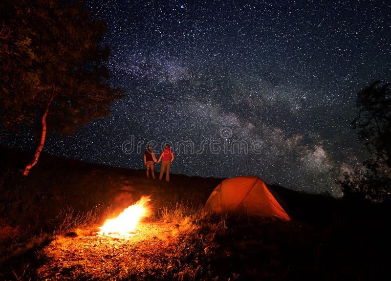 Natt som campar med en lägereld under en ljus stjärnklar himmel med den ljusa mjölkaktiga vägen arkivfoton
