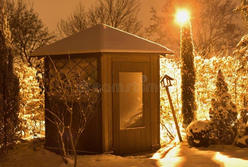 Nattbild av det rundade trädgårds- huset i vintertiden som täckas av snö och tänds av gatalampan med orange ljus royaltyfri foto