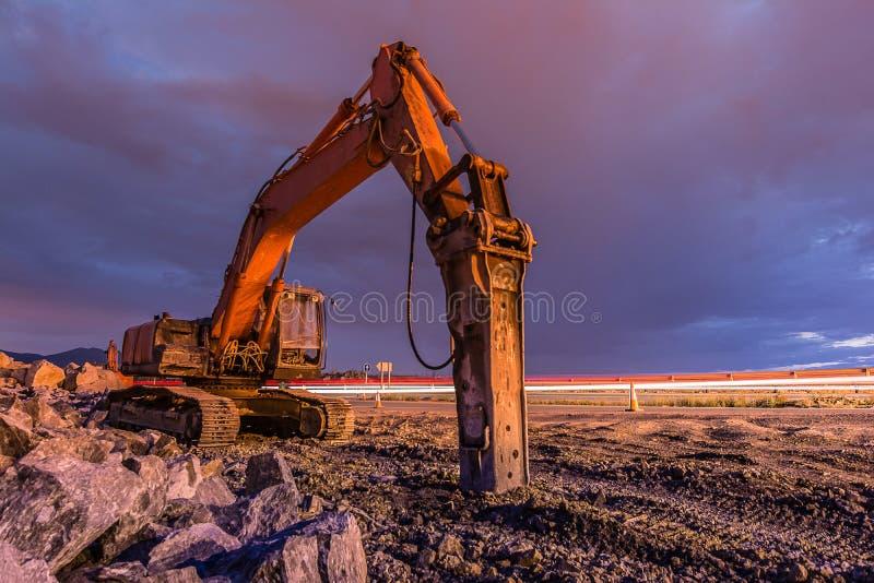 Nattbild av en hydraulisk hammare i arbetena av utvidgning av en väg royaltyfri fotografi