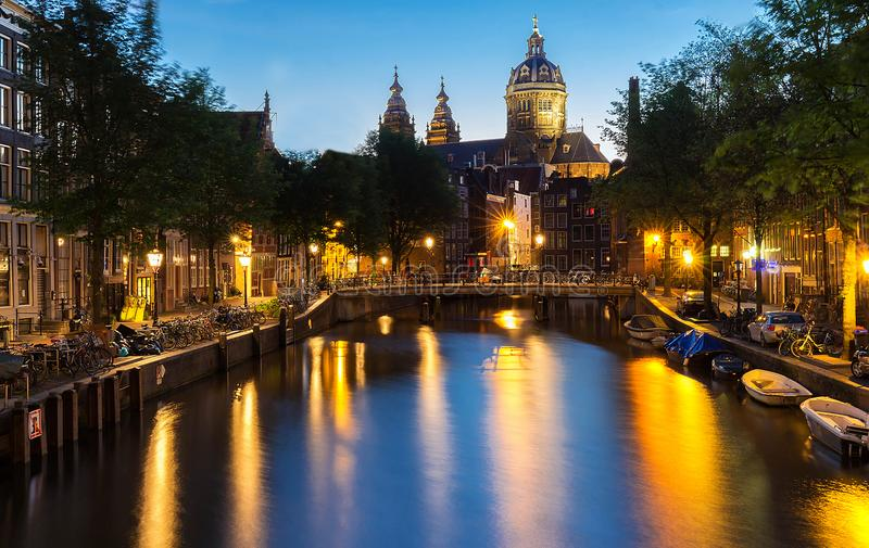 Nattbordellkvarter De Wallen, kanal, basilika av St Nicholas och bro, Amsterdam, Holland exponering long arkivfoto