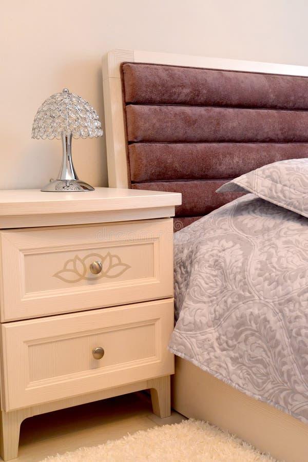 Nattduksbord med en skrivbordlampa i en sovruminre Skandinavisk stil arkivbilder