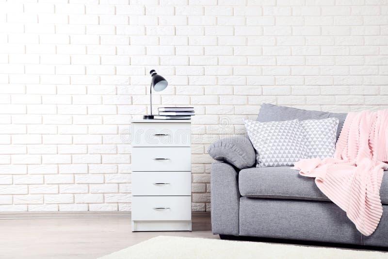 Nattduksbord nära den gråa soffan med kuddar royaltyfria foton