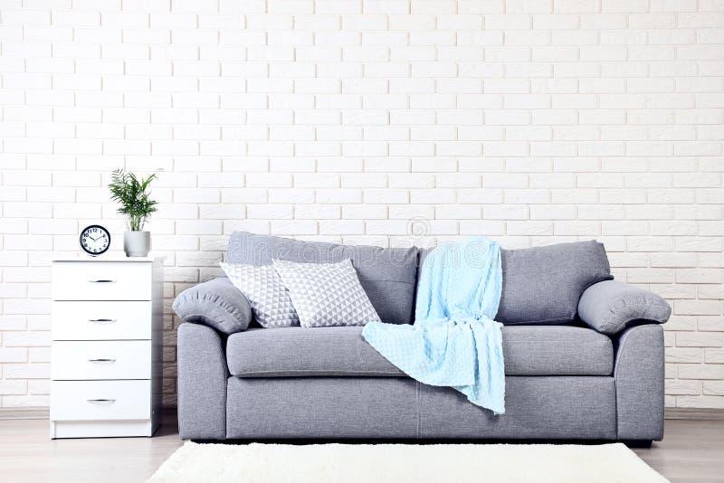 Nattduksbord nära soffan med kuddar royaltyfri foto