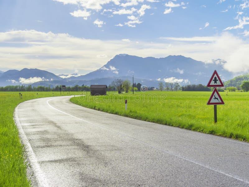 Natte asfaltweg na regen bij het platteland met verkeersteken, groen gras rond en bergen op de horizon stock afbeelding