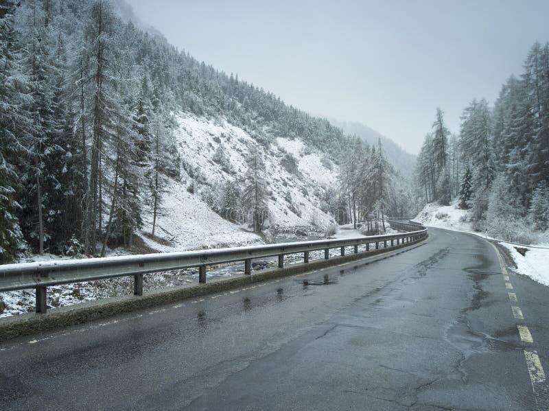 Natte de winterweg in Alpien stock afbeelding
