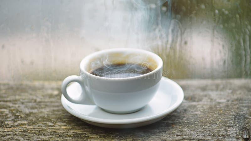 Natte glasvenster en kop van hete koffie De herfst bewolkt weer beter met cafe?nedrank Het genieten van van koffie op regenachtig royalty-vrije stock afbeeldingen