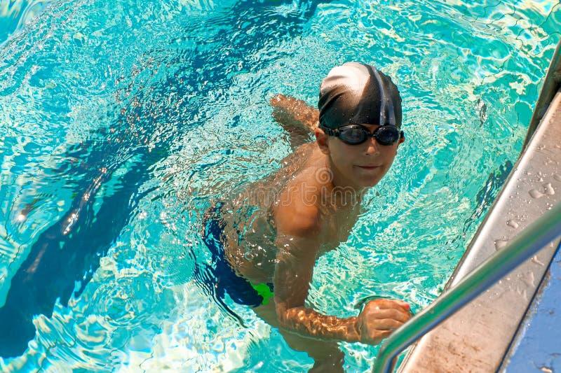 Natte jongen dichtbij metaalladder van zwembad van bovengenoemde mening, gestemd beeld stock afbeeldingen