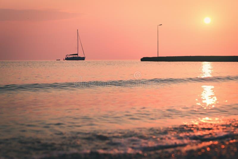 Natte kiezelsteenstenen en varende boot bij ochtendkust stock afbeelding