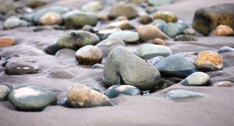 Natte rotsen op een vochtig zandig strand royalty-vrije stock afbeelding