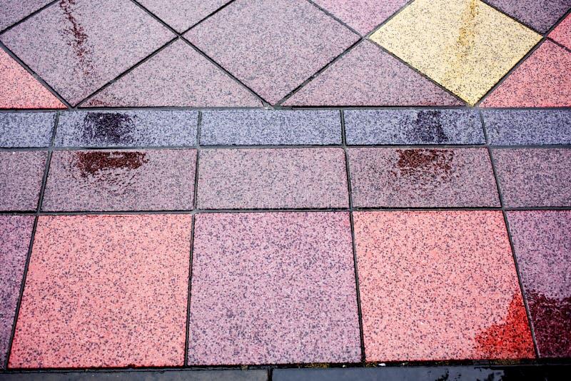 Natte vloer door regen met gekleurde tegels stock foto's