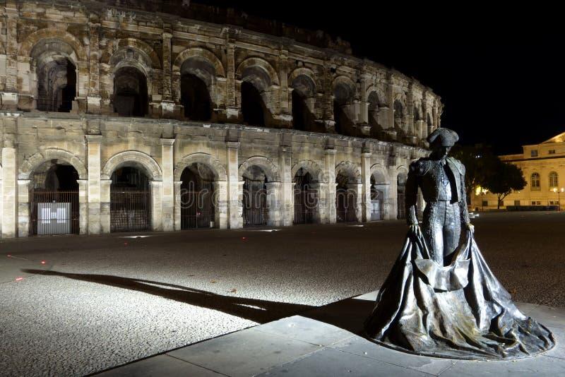 Natten beskådar arenan av Nîmes och statyn av matador royaltyfri foto