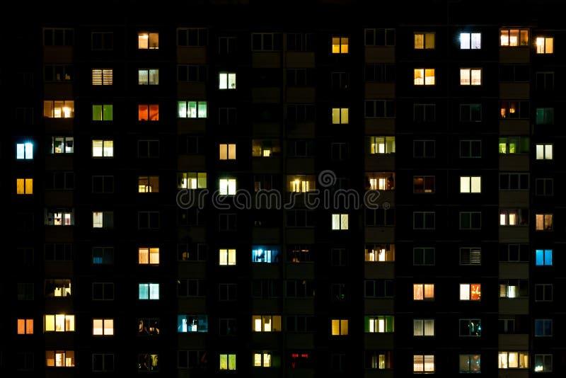 Nattetidschackningsperiod av ljus i f?nstren av en flerv?nings- byggnad Liv i en storstad arkivbild