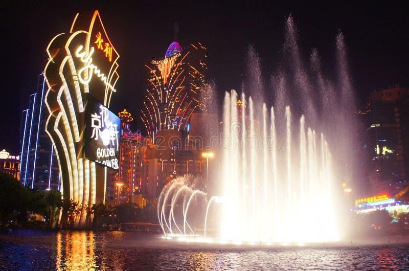 Nattfasaderna av den storslagna Lissabon Macao kasinosemesterorten och Wynn med kulöra dansfontains arkivfoton