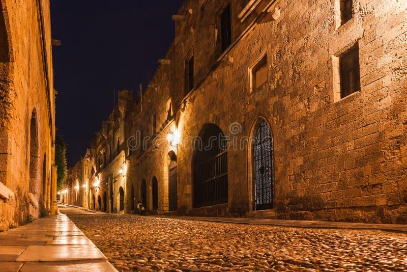 Nattfoto av den forntida gatan av riddarna i den Rhodes staden på den Rhodes ön, Dodecanese, Grekland Stenväggar och ljus natt royaltyfri fotografi