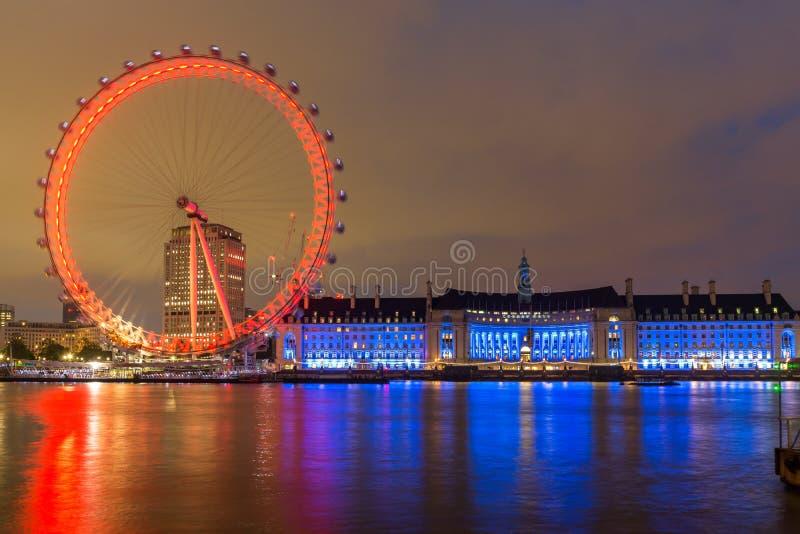 Nattfoto av det London ögat och den ståndsmässiga Hallen från den Westminster bron, London, England, stor britt royaltyfria foton