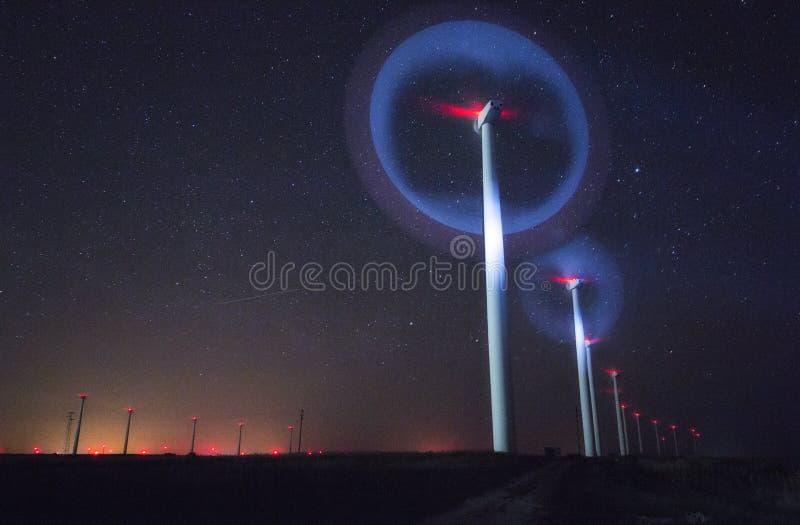 Nattfoto av vindgeneratorer och stjärnor med abstrakt belysning fotografering för bildbyråer