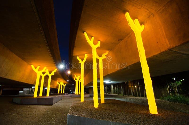 Nattfotografi av konstverk` aspirerar `-träd skulpterar glimt som är ljusa och som är guld- under betongen av motorvägen på Ultim arkivbild