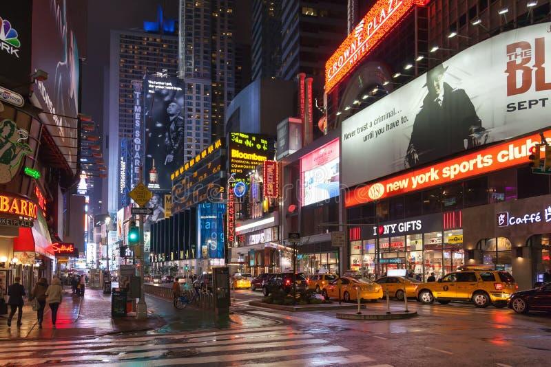 Nattgata broadway i New York Gul utomhus- taxi, många personer och annonsering arkivbild