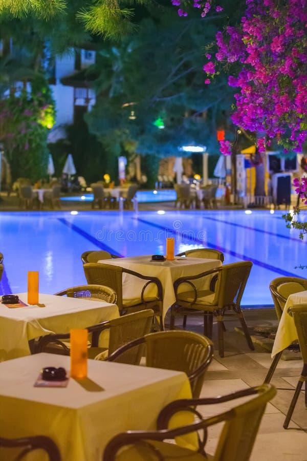 Nattkafét, tomma tabeller tjänade som för matställen, stearinljus, ljus, vid pölen i trädgården med palmträd, och blommor, afton  royaltyfri foto