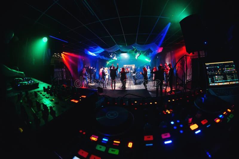 Nattklubb med dansfolk på dansgolv och etapp för musikalisk händelse- och blandarediscjockey arkivfoton