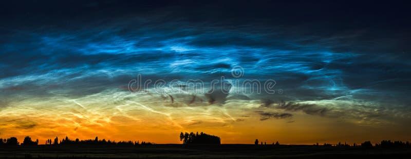 Nattlandskap med den elektriska linjen och Noctilucent moln på Litauen arkivfoto