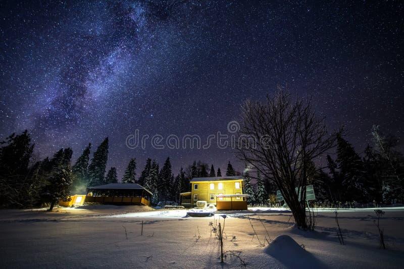 Nattlandskap med den färgrika Vintergatan ovanför det ensamma huset i mörk skog i Ryssland arkivbild