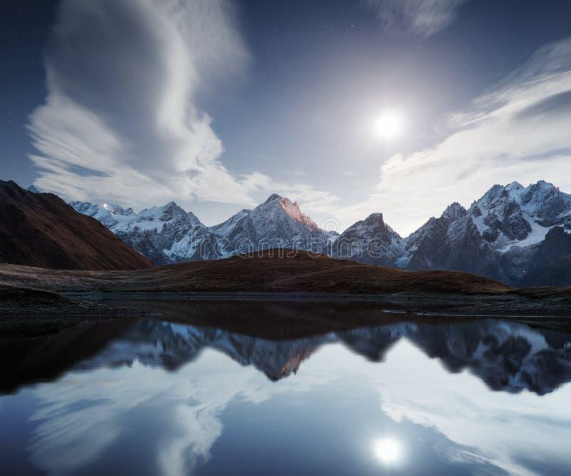Nattlandskap med en bergsjö och en måne royaltyfri foto