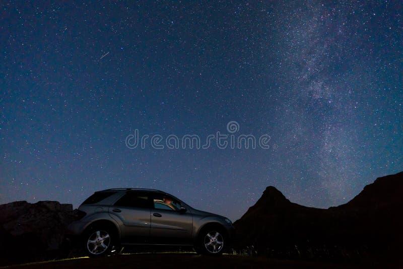 Nattlandskap med en bil på bakgrunden av den mjölkaktiga vägen royaltyfri bild