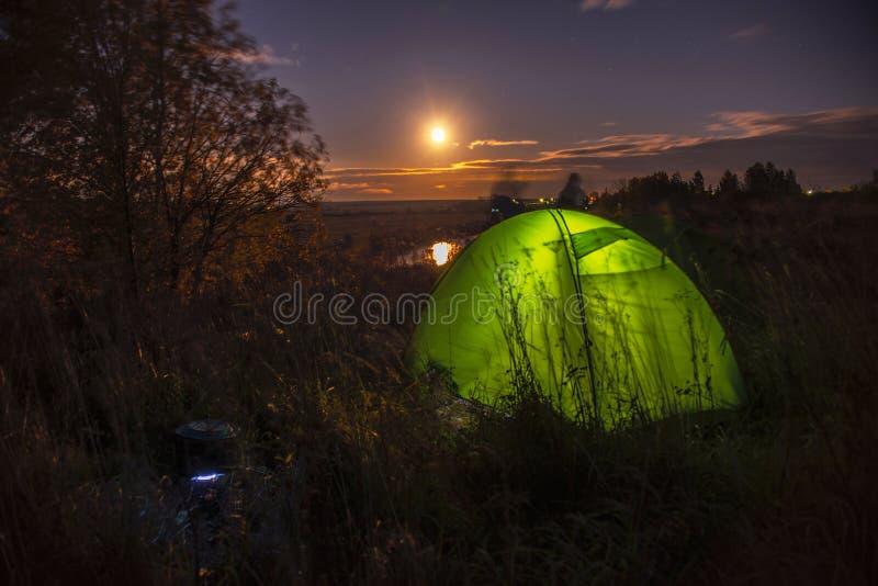 Nattlandskap med ett tält och en fullmåne nära den Nerl floden, Ryssland royaltyfri bild