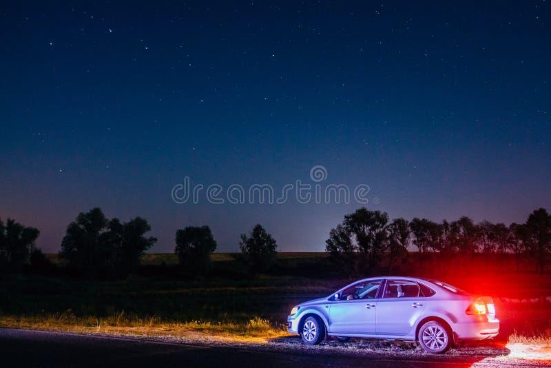 Nattlandskap med Volkswagen polo under stjärnorna Dobrush B royaltyfri bild