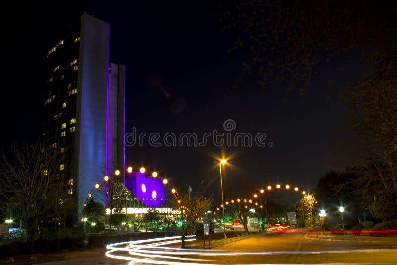 Nattlandskap på lång exponering Högväxt byggnad och bilar som passerar nattljusen fotografering för bildbyråer