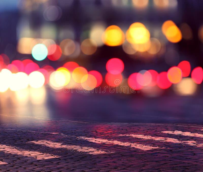 Nattljus i stad och zebramarkering arkivbild