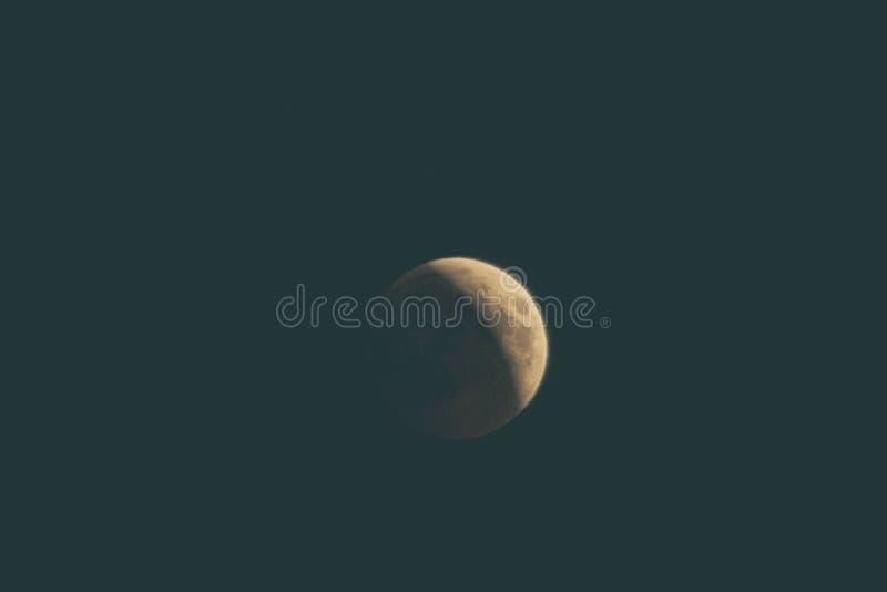 Nattmånförmörkelse på en mörk himmel arkivbild
