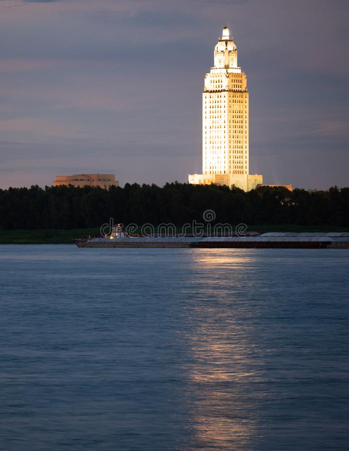 Nattnedgångar, medan en pråm reser ner Mississippi River royaltyfria bilder