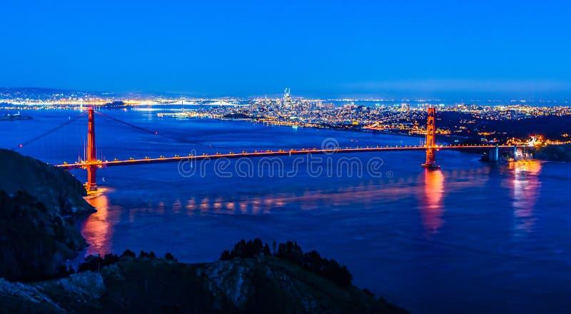 Nattpanoramautsikt av San Francisco och Golden gate bridge royaltyfri foto