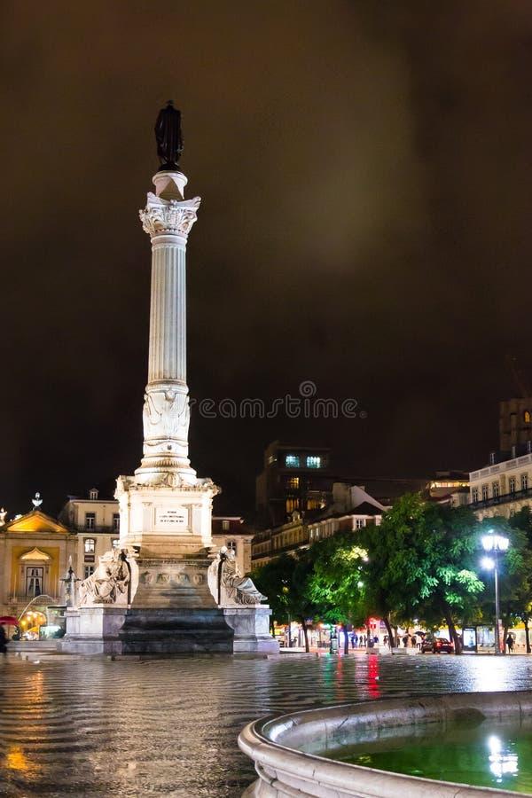 Nattplats av den Rossio fyrkanten, Lissabon, Portugal med en av dess dekorativa springbrunnar och kolonnen av den Pedro droppen royaltyfri bild