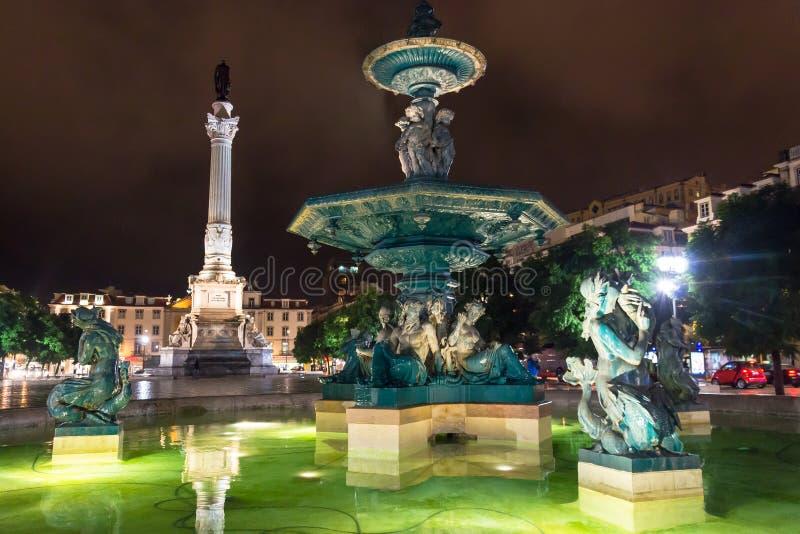 Nattplats av den Rossio fyrkanten, Lissabon, Portugal med en av dess dekorativa springbrunnar och kolonnen av den Pedro droppen royaltyfri fotografi