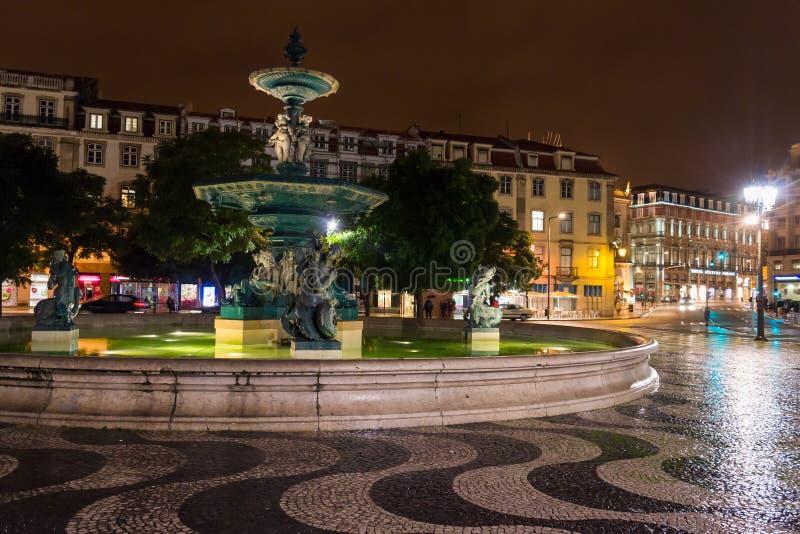 Nattplats av den Rossio fyrkanten, Lissabon, Portugal med en av dess dekorativa springbrunnar och kolonnen av den Pedro droppen arkivfoton