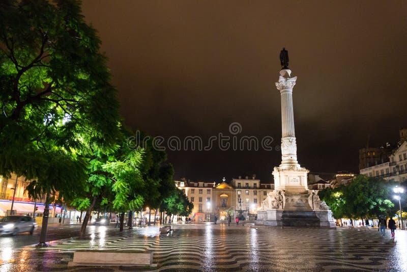 Nattplats av den Rossio fyrkanten, Lissabon, Portugal med en av dess dekorativa springbrunnar och kolonnen av den Pedro droppen fotografering för bildbyråer
